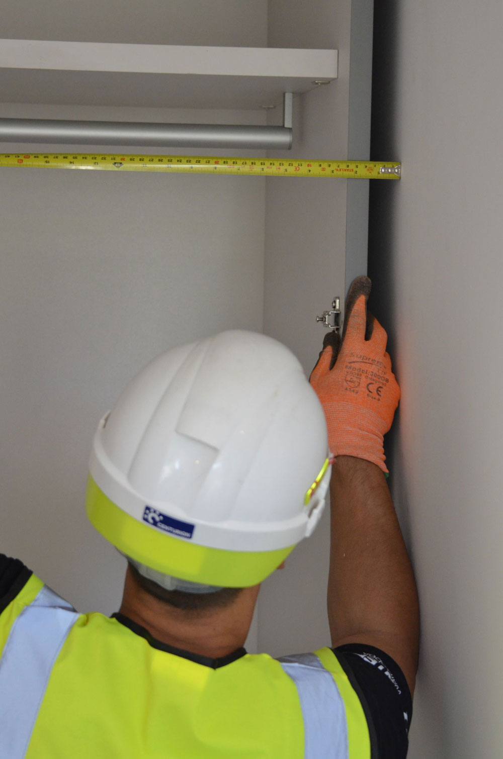 Image of a Pantera Wardrobes installer taking internal measurements